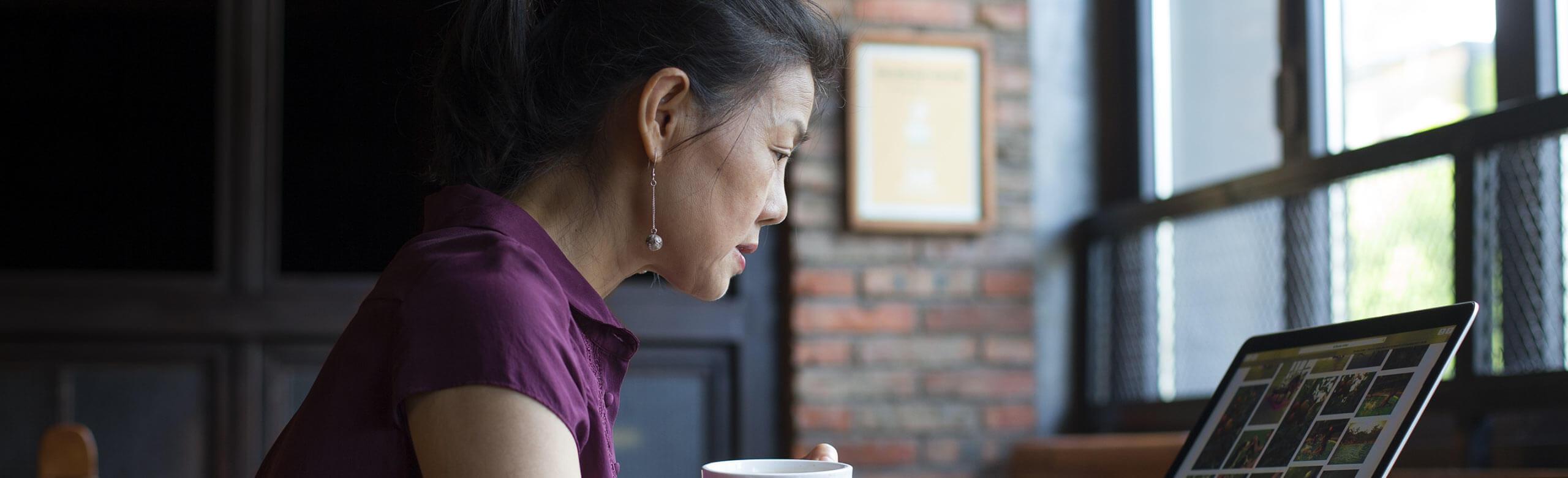在用筆電工作時喝咖啡的女人
