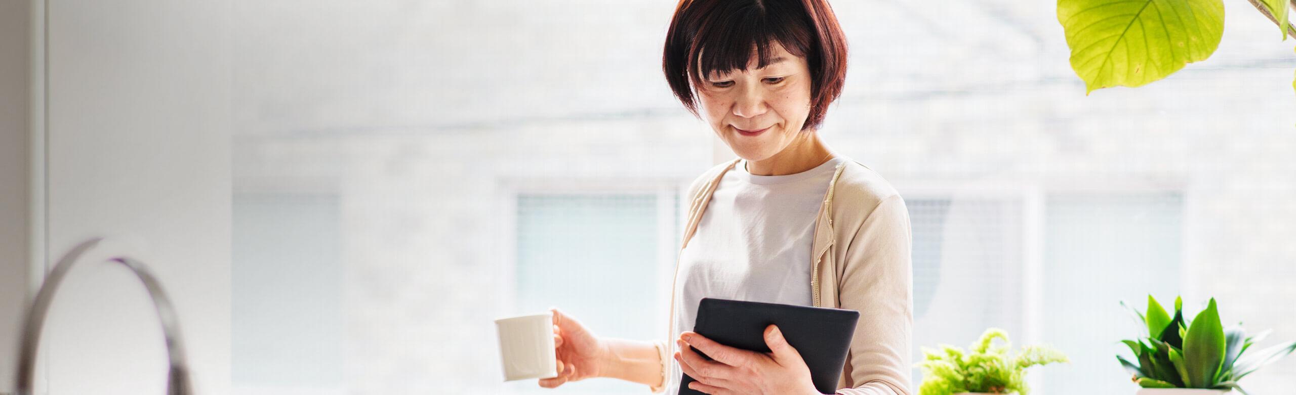 女人拿著咖啡杯和平板電腦